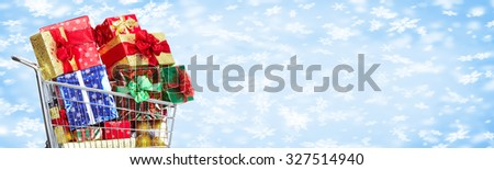 Shopping cart with Xmas gifts over snowy banner background. - stock photo