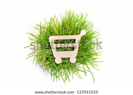 Shopping cart wooden icon and grass isolated on white background
