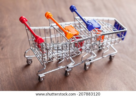Shopping carts on wooden surface - stock photo