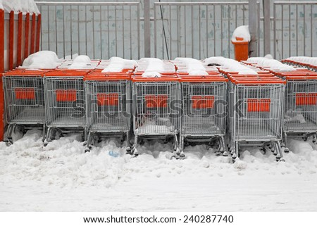 Shopping carts under the snow at supermarket parking lot - stock photo