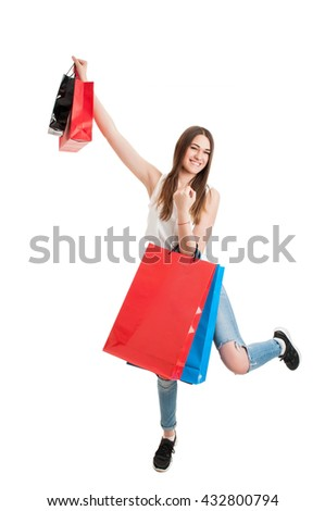 Shopping cheerful young woman holding colored bags over her head as sales or discount concept with copyspace isolated on white - stock photo