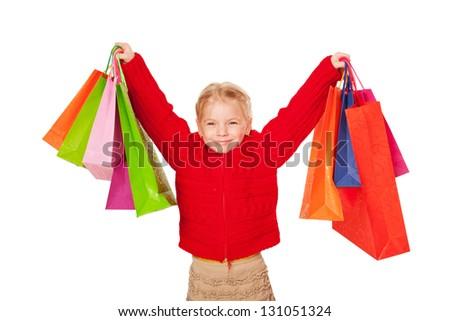 Shopping child. Happy little girl holding up shopping bags.  Isolated on white background - stock photo