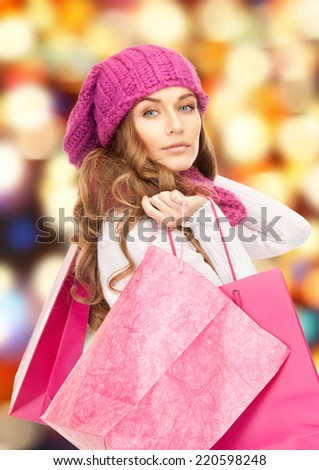 shopping, christmas sale and gifts concept - woman in winter clothes with pink shopping bags - stock photo