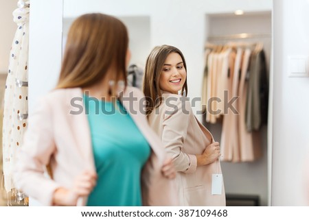 shopping, clothes, fashion, style and people concept - happy woman choosing jacket and posing at mirror in mall or clothing store