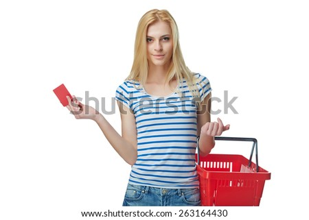 Shopping concept. Happy woman standing with empty red shopping basket and showing blank credit card, white background - stock photo