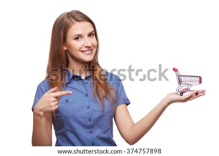Shopping concept. Portrait of smiling woman holding small empty shopping cart on her palm and pointing at it, isolated on white background - stock photo