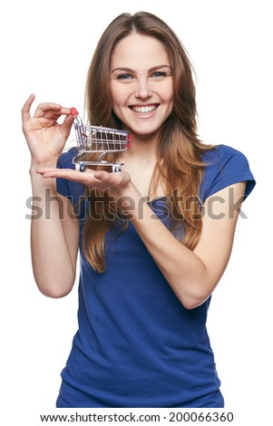 Shopping concept. Smiling happy young woman showing small empty supermarket shopping cart on her palm, over white background - stock photo