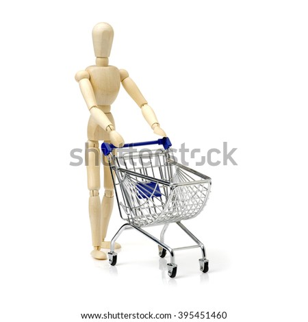 Shopping concept. Wooden doll and metal shopping cart. - stock photo