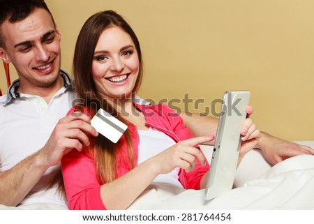 Shopping consumerism leisure and people concept. Young couple with tablet pc and credit card on sofe at home doing shopping on internet
