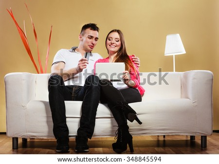 Shopping, consumerism, leisure and people concept. Young couple with tablet pc and credit card on sofe at home doing shopping on internet - stock photo