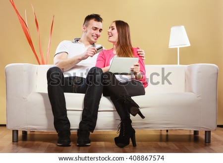Shopping consumerism leisure and people concept. Young couple with tablet pc and credit card on sofe at home doing shopping on internet - stock photo
