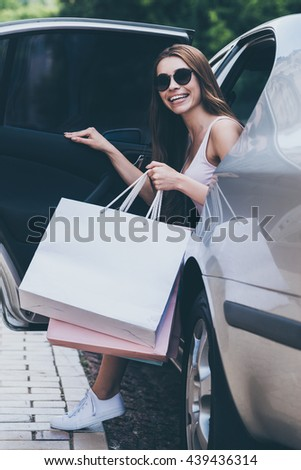 Shopping day is just starting. Beautiful young smiling woman carrying shopping bags and opening door car door while sitting inside of it  - stock photo