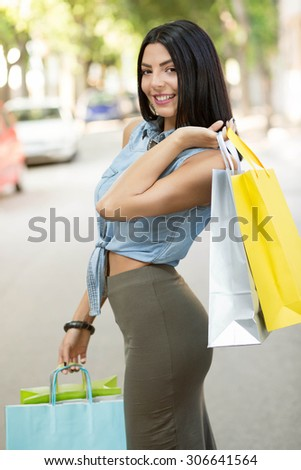 Shopping fan. Attractive young woman posing on a city street with lots of colorful shopping bags. - stock photo