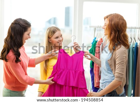 shopping, fashion and friendship concept - three smiling friends trying on some clothes at home or shopping mall - stock photo