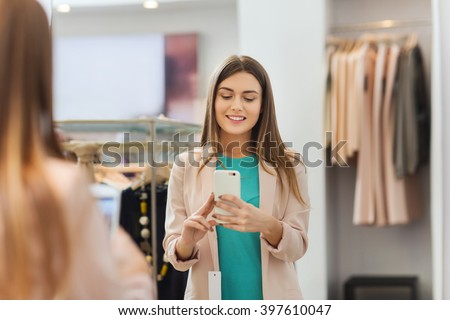 shopping, fashion, style, technology and people concept - happy woman with smartphone taking mirror selfie at clothing store