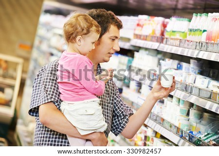 Shopping. Father man and little child girl choosing dairy products in shop supermarket
