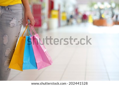 Shopping! Female Hand Holding Colorful Shopping Bags in Shopping Mall - stock photo