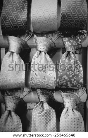 Shopping for elegant dressing accessories. Ties at a shop in Italy. Formal wear selection in a store. Black and white tone - retro monochrome color style. - stock photo