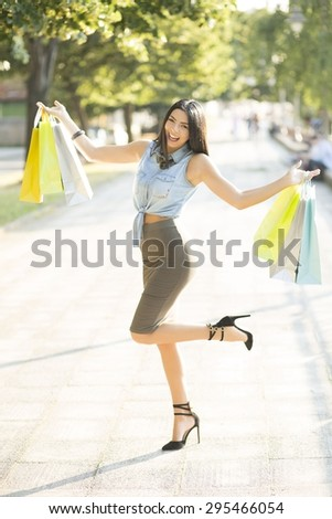 Shopping girl. Cheerful young fashionable woman posing on the city streets, carrying a shopping bags. - stock photo