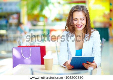 Shopping girl laughing looking at the screen of her portable device
