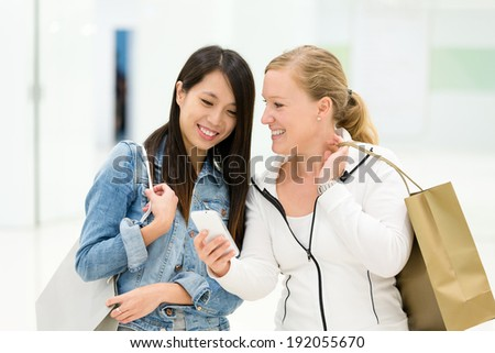 Shopping girl looking at cellphone - stock photo