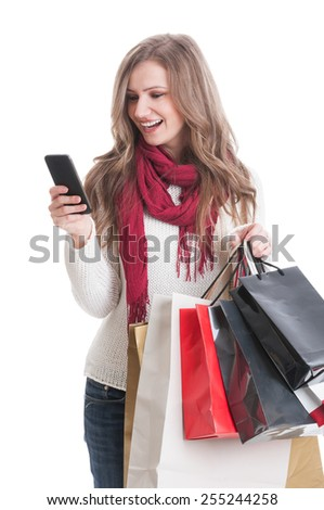 Shopping girl texting about the sales to her friends while smiling on white background - stock photo