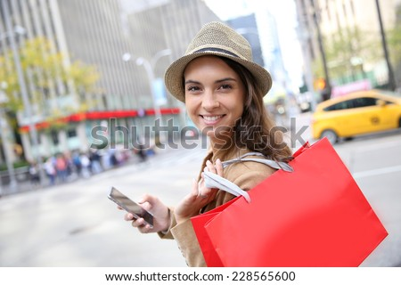 Shopping girl with red bag and smartphone in Manhattan - stock photo