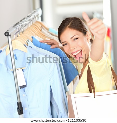 Shopping - Happy shopper woman showing thumbs up excited holding shopping bag in clothing store looking for clothes on sale. Beautiful mixed race asian caucasian woman model.
