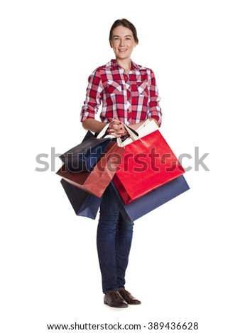 Shopping. Happy young brunette woman with colorful shopping bags in blue jeans and shirt posing isolated on a white background