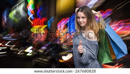 Shopping in New York City. Beautiful young woman with shopping bags during sales season in the big city at night - stock photo