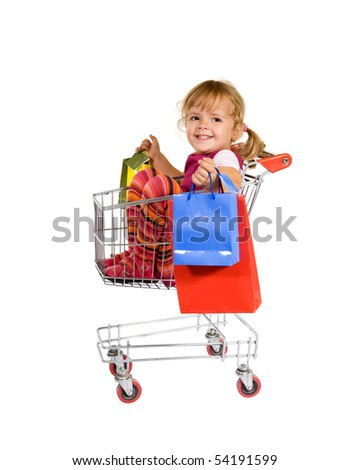 Shopping is fun - little girl sitting in a cart with colorful bags - stock photo