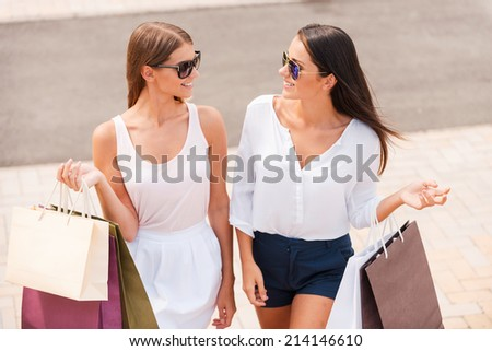 Shopping is the best therapy. Top view of two beautiful young women with shopping bags walking together and talking - stock photo