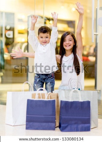 Shopping kids with arms up looking very happy - stock photo