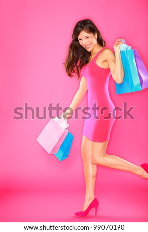 Shopping lady. Woman shopper holding shopping bags walking smiling happy and joyful in full length on pink background. Young beautiful mixed race Asian / Caucasian female fashion model.