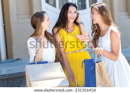 Shopping last news. Three young and pretty girls are talking to each other about best sales offers in shops and smiling. All are in a great mood - stock photo