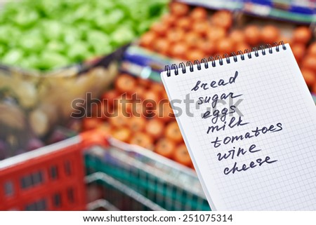 Shopping list in the hands of a woman in a supermarket - stock photo