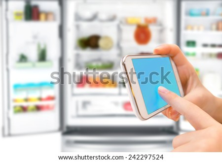 Shopping list on his phone connected to the refrigerator. - stock photo