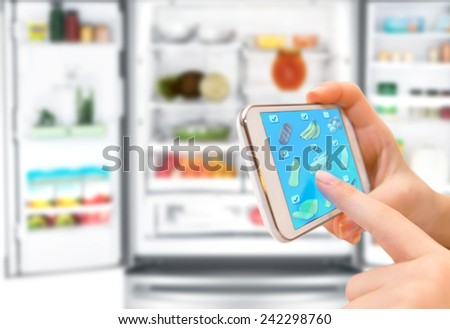 shopping list on his phone connected to the refrigerator - stock photo