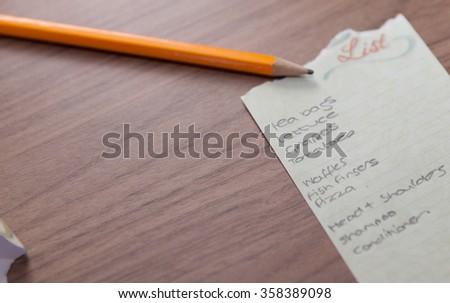 shopping list on wood ackground shot - stock photo