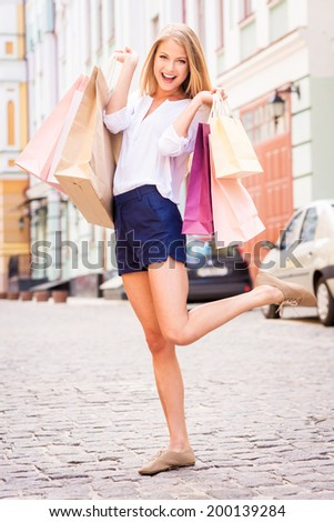 Shopping makes me happy! Full length of attractive young cheerful woman holding shopping bags and looking at camera while standing outdoors - stock photo