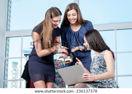 Shopping of new shoes. Girlfriends shopaholics choose new shoes in a laptop while girlfriend show each other new purchase. Girls having fun together doing shopping - stock photo