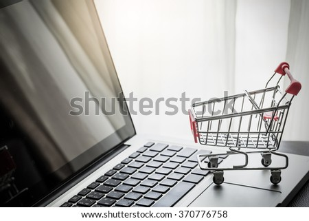 Shopping Online Concept : Mini Shopping Cart On Laptop - stock photo