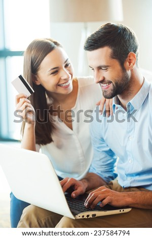 Shopping online together. Beautiful young loving couple shopping online together while woman holding credit card and smiling - stock photo