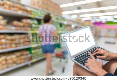 Shopping Online With Digital laptop on Abstract blurred photo of store with trolley in department store bokeh background, technology and internet concept - stock photo