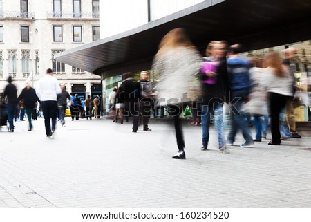 shopping people walking on the sidewalk of a shopping street - stock photo