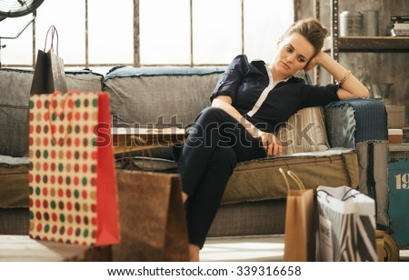 Shopping relieving stress? Tired frustrated brunette woman in elegant clothing sitting on couch among shopping bags in loft apartment. - stock photo