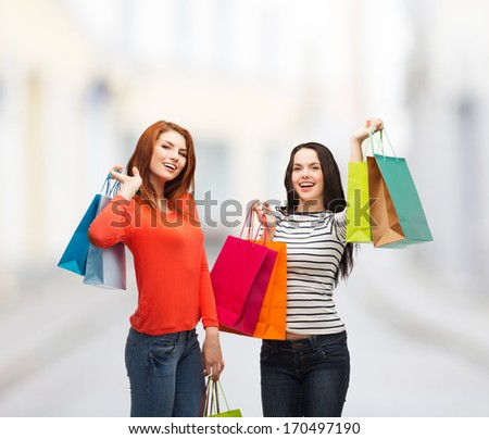 shopping, sale and gifts concept - two smiling teenage girls with shopping bags at street - stock photo