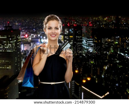 shopping, sale, banking, money and holidays concept - smiling woman in dress with shopping bags and credit card over black background - stock photo