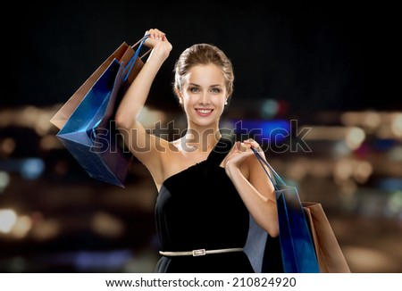 shopping, sale, gifts and holidays concept - smiling woman in dress with shopping bags over black background - stock photo