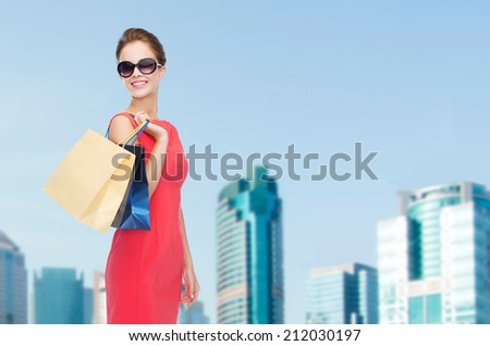 shopping, sale, gifts and holidays concept - smiling woman in red dress and sunglasses with shopping bags